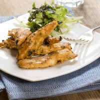 Delicious chicken strips with a side salad on a white square plate on a blue placemat